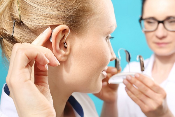 a young woman trying on types of hearing aids and selecting the best one