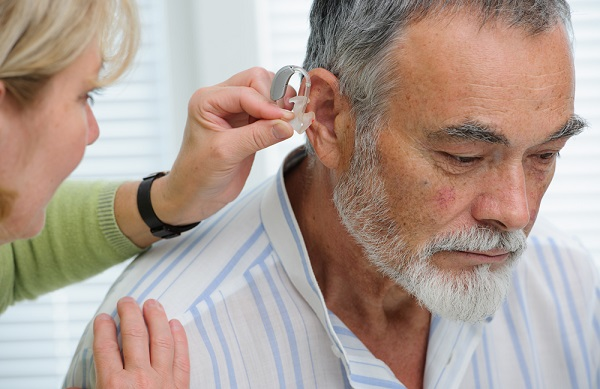 audiologist inserting hearing aid in senior's ear. getting used to wearing a hearing aid.