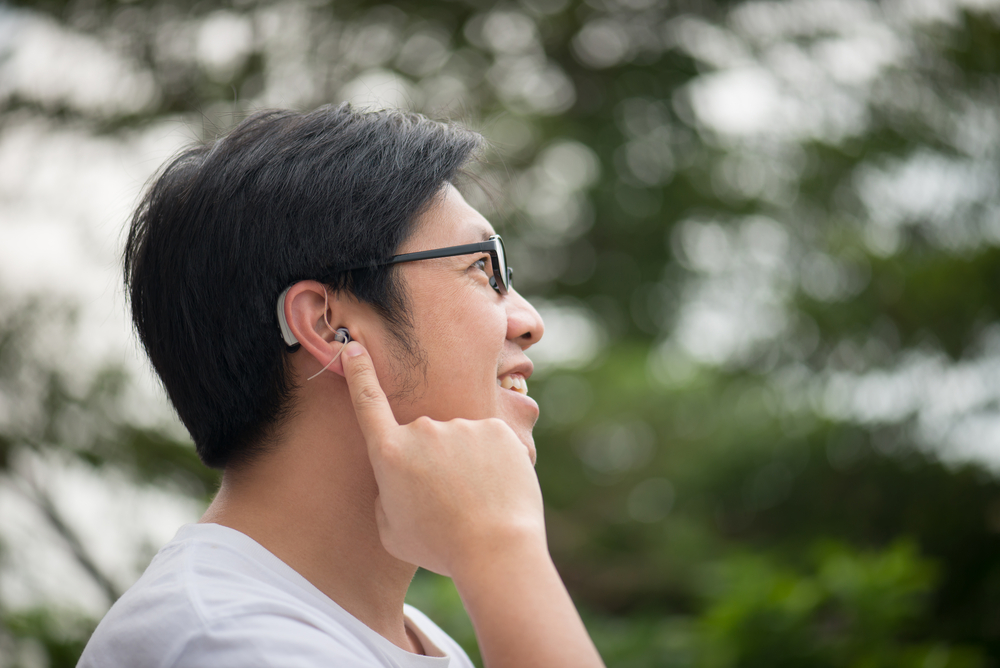 Man with eye glasses and hearing aid on his ear.